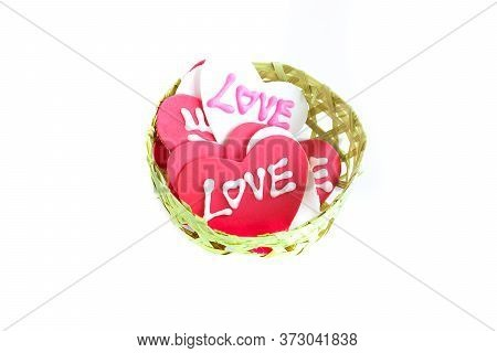 A Piles Of Sugary Heart-shaped Love Signs In A Small Handmade Bamboo Busket, Isolated On White Backg