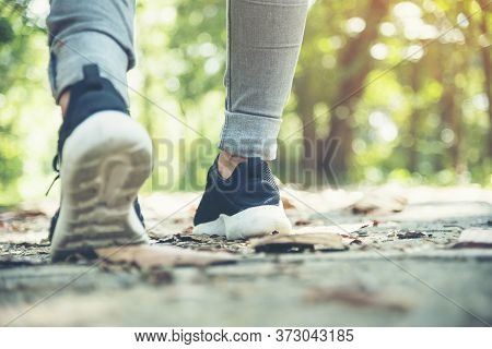 Sneaker Shoes Young Woman Traveler Sit Down On Summer Park. Focus On Sneaker Shoes And Jeans On Path