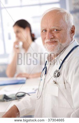 Portrait of senior doctor smiling at doctor's room.