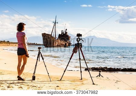 Tourist Woman Photographer With Professional Cameras On Tripods Taking Picture Film Video From Coast