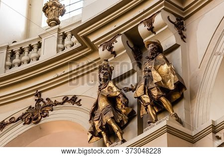 Lviv, Ukraine - October 23, 2019: Gilded Male Statues In Dominican Church Near Arches And Balustrade