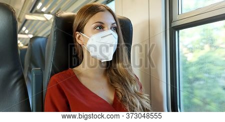 Travel Safely On Public Transport. Young Woman With Kn95 Ffp2 Face Mask Looking Through Train Window