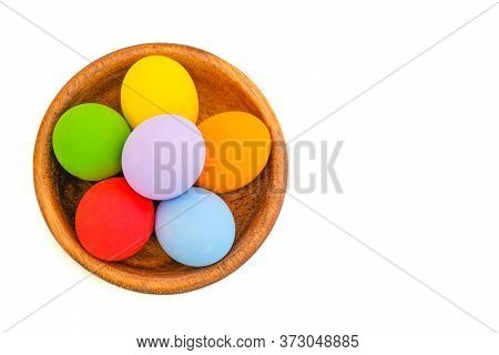 Assortments Of Colorful Painted Ester Eggs In A Teak Bowl, Isolated On White Background