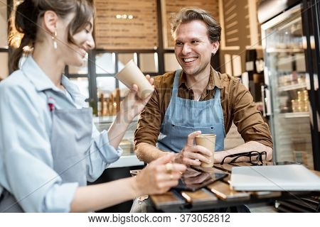 Couple Of A Young Cafe Workers Have Some Business Conversation While Sitting With Coffee At The Tabl