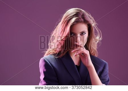 Portrait of a charming girl with bright make-up and beautiful wavy hair on a lilac-purple background. Studio beauty portrait. Make-up and cosmetics. Copy space.