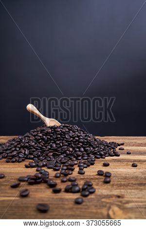 Wooden Spoon Put On Pile Of Coffee Bean Black Background