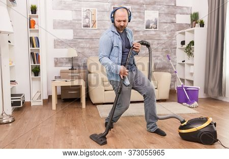 Excited Man Cleaning House And Listening Music On Headphones.