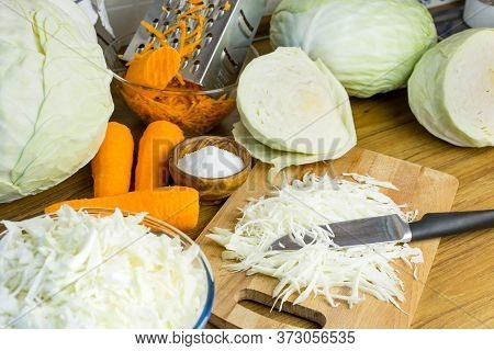 Ingredients For Salting Cabbage. Sliced Cabbage, Carrots And Salt On The Kitchen Table Are Ready For