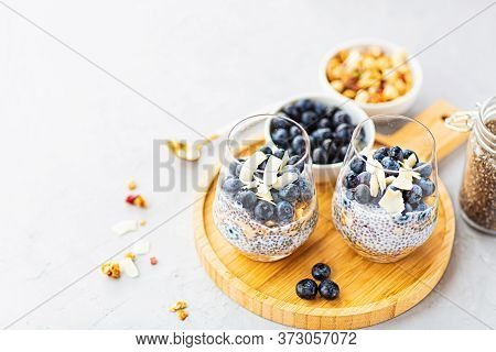Chia Pudding With Granola And Fresh Blueberries In The Glasses On A Gray Concrete Background With Co