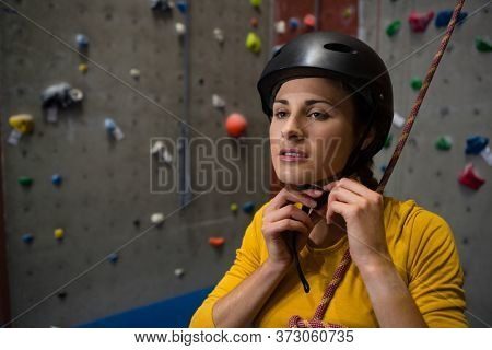 Confident female athlete wearing sports helmet in health club
