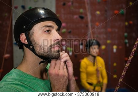 Male athlete looking away while wearing sports helmet in health club