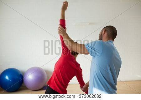 Rear view of male instructor assisting student in exercising at health club