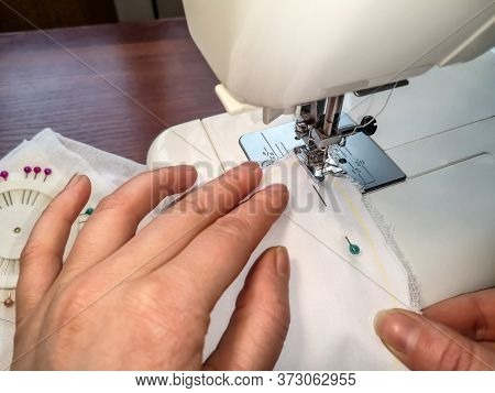 Sewing Machine Scribbles A White Cloth Fastened With A Sewing Pin, Close-up. Female Hands Sew A Sewi