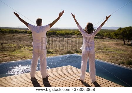 Rear view of couple standing with arms outstretched near poolside on a sunny day