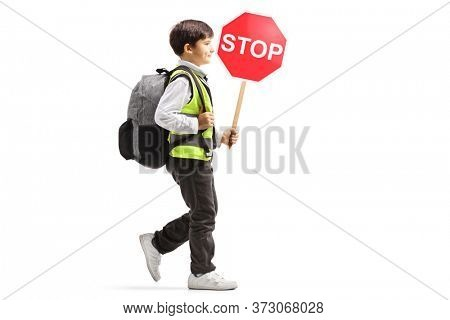 Full length profile shot of a schoolboy wearing a safety vest and a stop sign and walking isolated on white background