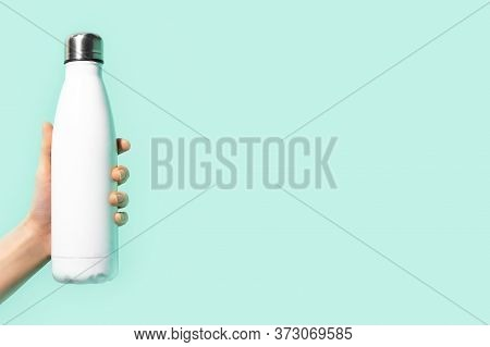 Close-up Of Female Hand Holding A Reusable Steel, Eco Thermo Water Bottle Of White, Isolated On Back
