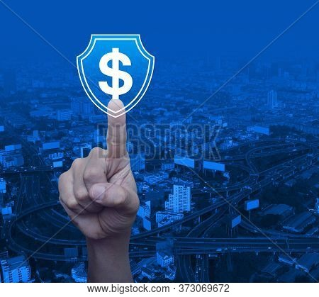 Hand Pressing Dollar With Shield Flat Icon Over Modern City Tower, Street, Expressway And Skyscraper