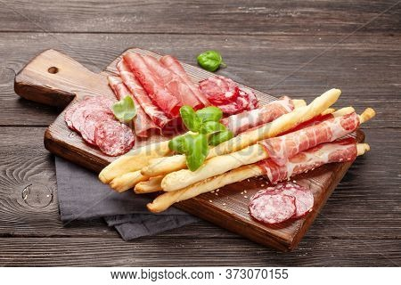 Various meat antipasto. Appetizer selection board with salami, prosciutto and parma jamon