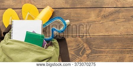 Travel Planning Concept. Backpack With Blank Notebook And Traveler Accessories On Wooden Table. Copy