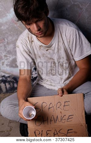 Dirty young homeless guy asking for help and spare change, sitting on a street