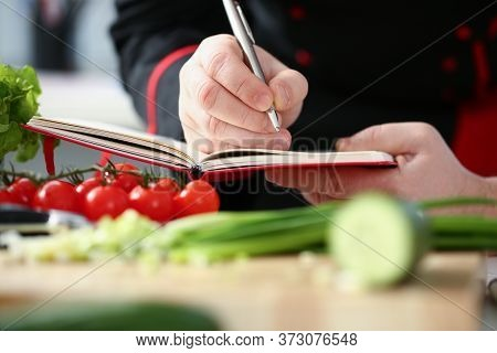 Close Up Of Young Man Holding Silver Pen And Notebook While Standing By The Table With Tomatoes And