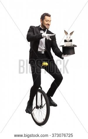 Magician riding a unicycle and performing a hat-trick with a rabbit isolated on white background