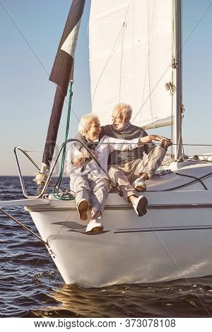 Sailing Is A Fun. A Happy Senior Couple Sitting On The Side Of A Sail Boat On A Calm Blue Sea. Man H