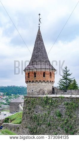 Tower With Spire Roof And Moss-covered Defensive Wall Of Medieval Castle. Kamianets-podilskyi City,