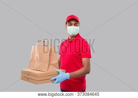Delivery Man With Paper Bag And Three Pizza Box In Hands Wearing Medical Mask And Gloves Isolated. R