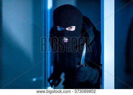 Homicide Concept. Murder In Black Balaclava Hat Breaking Into House At Night, Holding Knife In The D