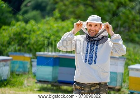 Beekeeper In Protective Workwear. Hives Background At Apiary. Works On The Apiaries In The Spring