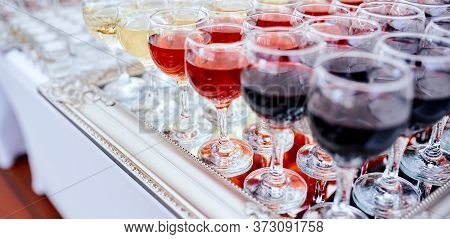 Many Vine Glasses Filled With Red And White Vine And Glasses Filled On The Mirror Tablecloth. Cateri
