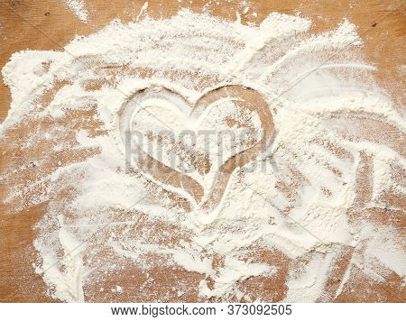 Sprinkled White Wheat Flour On A Brown Wooden Background, A Heart Is Drawn With A Finger, Top View