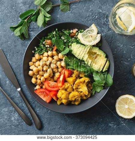Buddha Bowl Vegetarian Healthy Balanced Food Aloo Gobi, Chickpeas, Tomato, Avocado, Tabule Salad Spi