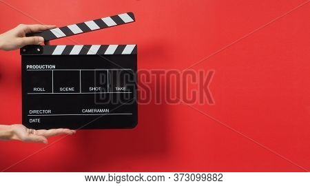 A Hand Is Holding Black Clapper Board Or Movie Slate On Red Background.it Used In Cinema Industry An