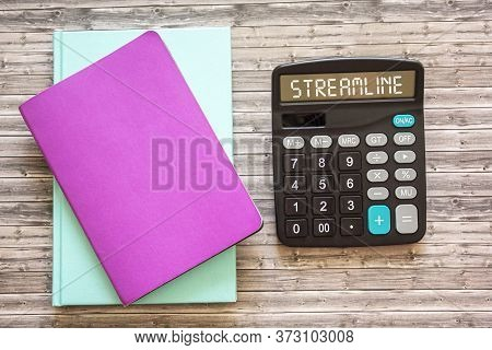 Streamlined Text On Calculator, Next To Colored Weeklies On Wooden Background