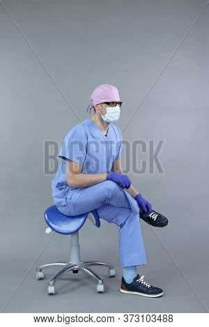 Exercise for dentist on chair in sitting position.Caucasian dentist in uniform, mask and eyeglasses , stretching leg   in studio - healthy lifestyle at work.