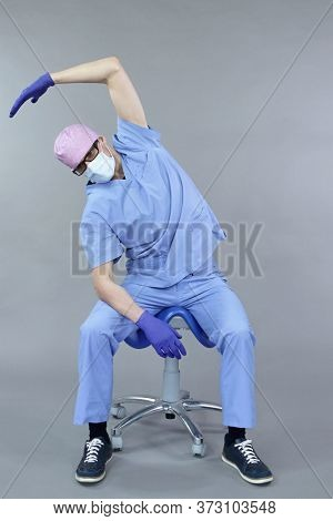 Exercise for dentist on chair.Caucasian dentist in uniform, mask and eyeglasses , stretching arm, neck and back   in studio - healthy lifestyle at work.