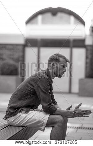 Young Man Sits And Ponders On Bench Against Background Of Modern Building. Black And White Image..