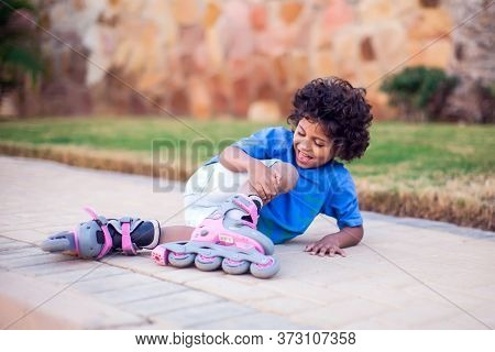 A Kid Boy On Rollerskates Fell Down And Feels Pain. Children, Activity And Healthcare Concept