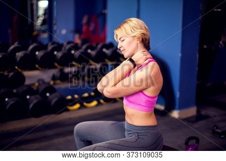 Woman With Short Blond Hair In Pink Top Feeling Strong Neck Pain While Training In The Gym. People,
