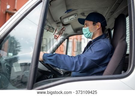 Masked truck driver giving driving a van during coronavirus pandemic