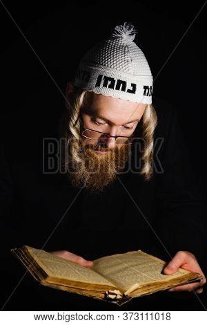 Hasidic Jew Reading The Torah. Religious Orthodox Jew With Sidelocks And Red Beard In White Bale Pra