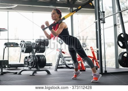 Athlete Woman Training Exercising With Suspension System Indoor Gym. Beautiful Caucasian Sportive Wo