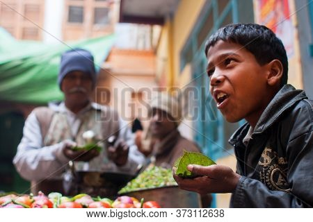 Varanasi, India: Boy Eating Fast-food Meals With Spicy Vegetables On Street With Street Food Traders