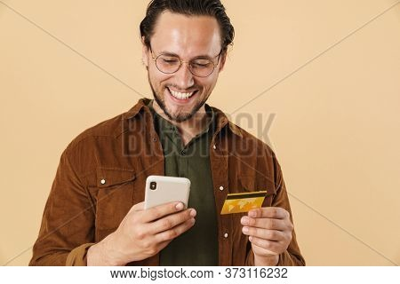 Image of cheerful bristle man holding credit card and using cellphone isolated over beige background