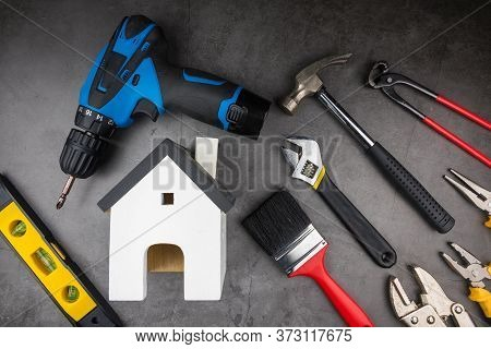 Wooden Model White Houses And House Cleaning Equipment On Cement Gray Background. Concept Clean Hous