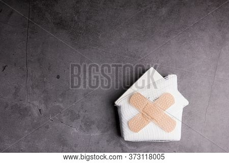 Wooden Model White Houses And First Aid Equipment On A Cement Gray Background. Concept Home Repair,