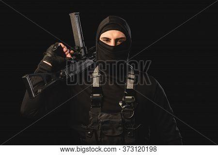 Terrorism In Body Armor And Balaclava Holding Machine Gun Isolated On Black
