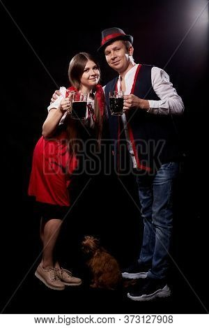 Funny Oktoberfest Couple In National Ethnic Dress With Mugs Of Beer, Small Shaggy Dog On Black Backg